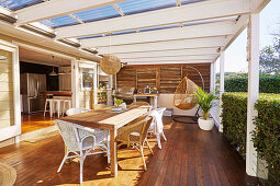 Wooden terrace with dining table, wicker furniture and outdoor kitchen