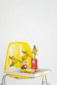 Tin cans used as vases on tray and yellow chair