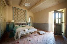 Open door in Mediterranean bedroom with terracotta-tiled floor