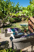 Two wicker sofas under pergola in Mediterranean garden