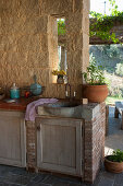 Stone sink and masonry units in outdoor kitchen on roofed terrace