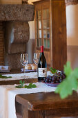 White bottle, glasses and grapes on rustic wooden table