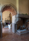 Fireplace next to arched, masonry doorway leading into living room