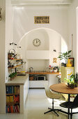 Round table, classic chairs, kitchen counter with concrete worksurface and mobile gas cooker in kitchen with arched doorway