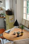 Runder Tisch mit Laptop, Zimmerpflanze und kleinem Globus unter Pendelleuchte