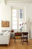 Gedeckter Tisch mit Orchidee vor Sprossenfenster, Stehlampe und Sofa in Altbauwohnung