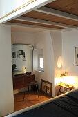 Blick über Bett auf beleuchteten Nachttisch, im Hintergrund 50er Jahre Kommode mit Wandpsiegel und Hocker