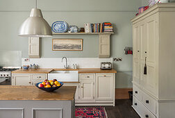Country-house kitchen with beige panelled cupboards and island counter