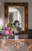 Bust and vase of flowers on carved, antique console table