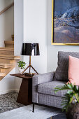 Upholstered armchair and elegant side table with lamp in front of stairs