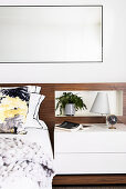 Double bed with elegant wooden headboard and bedside tables, large mirror above in the living room