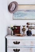 Jewelery on a vintage wooden chest of drawers, picture and hat above