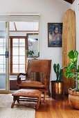 Vintage leather armchair with ottoman next to house plants and surfboard in corner of room