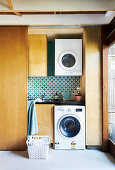 Laundry room behind a sliding door with hanging washing machine