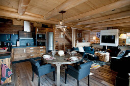 Open-plan kitchen in large interior of rustic log cabin