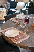Cutlery with horn handles on place mats on round, rustic wooden table