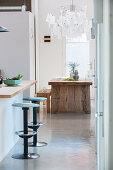 Bar stools at kitchen counter with rustic dining table in background