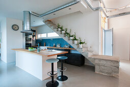 Open-plan, industrial-style kitchen below concrete staircase and extractor hood duct