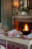Table set for afternoon coffee in front of roaring fire in open fireplace