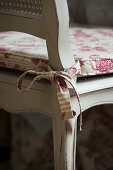 Patterned seat cushion tied to old wooden chair with bow