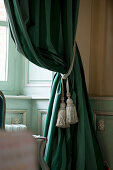 Classic tassels on dark green curtains against panelled wall