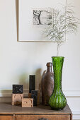 Grass in green vase and letter stamps decorating chest of drawers