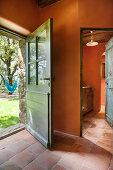 View of hammock in garden through open exterior door