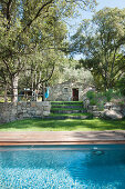 Swimming pool surrounded by wooden decking in Mediterranean garden with stone house in background