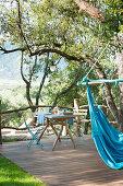 Blue hammock and set breakfast table on wooden terrace