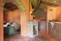 Mediterranean kitchen with terracotta tiles, fireplace and view into bedroom through open arched doorway