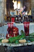 Red carafe and glasses amongst green fir branches in front of open fire