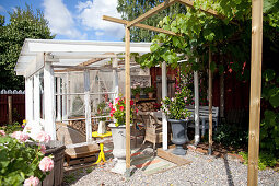 Vines growing on pergola leading to roofed terrace