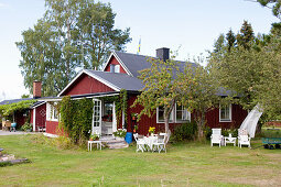 Falu-red Swedish house with seating areas in summery garden