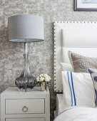 Elegant bedside lamp with glass base next to bed with white headboard