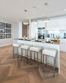 Island counter and designer bar stools in elegant white fitted kitchen