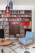 Retrosessel und runder Couchtisch vor Bücherregal mit roter Rückwand