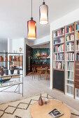 Blick vom Wohnzimmer mit Bücherwand in die offene Küche