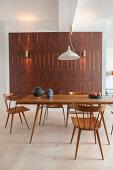 Verschiedene Holzstühle und Esstisch vor einer Wand mit Holzverkleidung