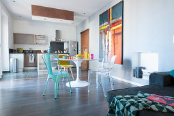 Dining table and open-plan kitchen in spacious interior
