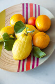 Citrus fruits on bamboo dish with colourful stripes