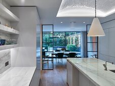 Glass and steel partitions and marble island counter in modern kitchen