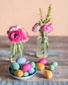 Colourful speckled eggs in bowl in front of posies of ranunculus