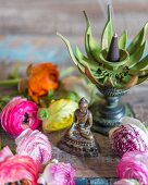 Small Buddha figurine, incense burner and ranunculus flowers on wooden surface
