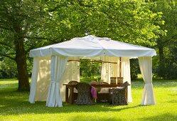 Wicker furniture in elegant white pavilion on summer lawn