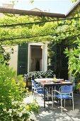 Begrünter Terrassenplatz mit Tisch und Stühlen und blühenden Pflanzen