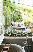 Blick aus Badfenster auf begrünte südländische Terrasse
