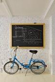 Blue folding bike below architect's plan on chalkboard