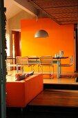 Esstisch vor orangefarbener Wand auf einer höheren Ebene