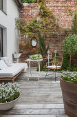 Inviting terrace adjoining house and exposed brick wall