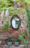 Oval mirror with ornate frame on exposed brick wall in garden
